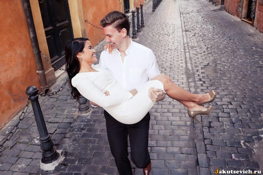 Парень несет любимую на руках в Риме